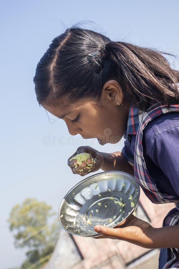 Indian school girl are eating food. royalty free stock images