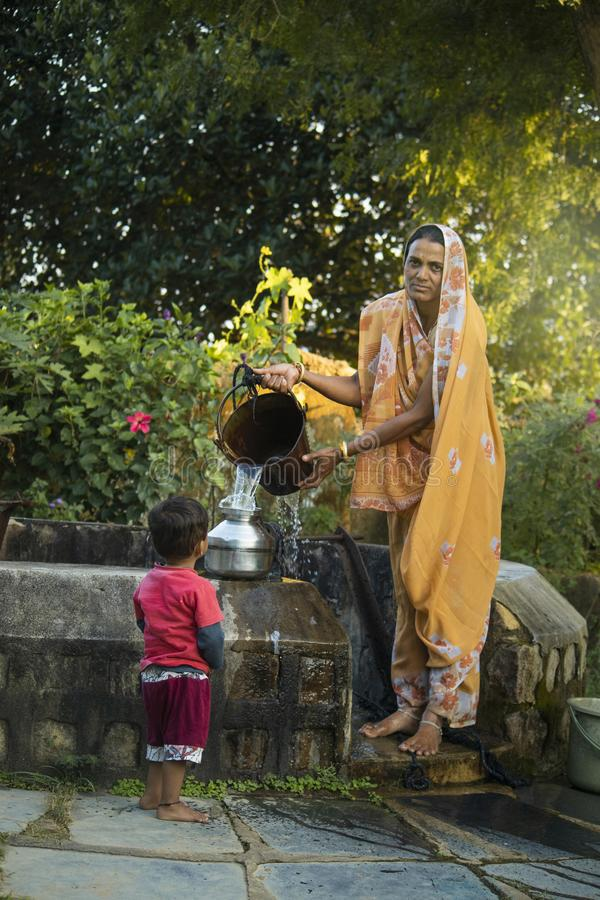 Indian woman filling water buckets at village well. stock photography