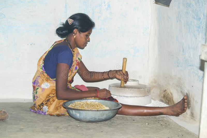 Rural Indian woman use hand mill to grind maize. stock photography