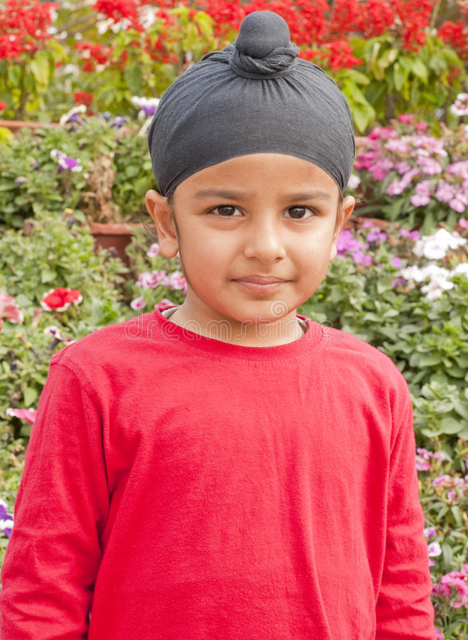 A Sikh boy standing ahead of flowers
