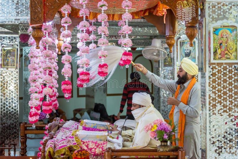 Sikh priest praying in Manikaran gurdwara in the Kullu District of Himachal Pradesh, India. Manikaran, India - June 3, 2017: Sikh priest praying in Manikaran royalty free stock images