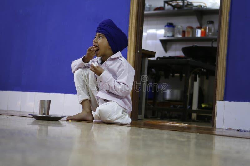Sikh- ung pojke som äter på templet under beröm arkivbilder