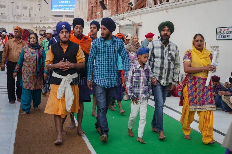 Sikhs и индийские люди посещая золотой висок стоковая фотография