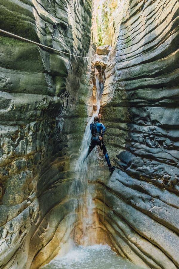 Siklawa Rappelling Mężczyzna w mokrym kostiumu wspina się na siklawie w wąskim rzecznym jarze obrazy stock