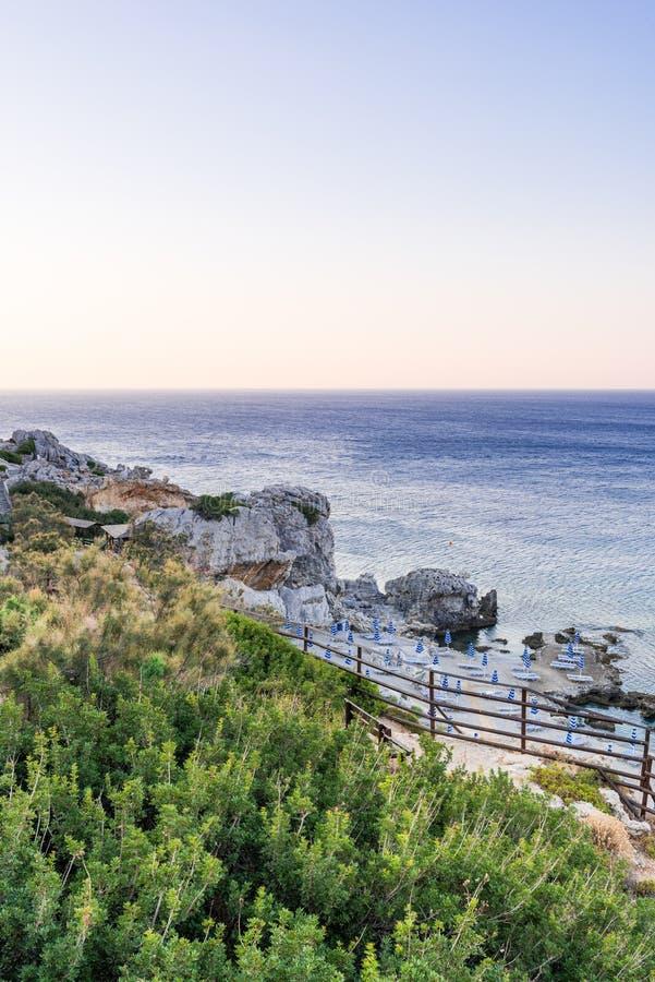Sikt över den blåa medelhavet och stranden med solsängar i Rhodes, Grekland royaltyfri bild