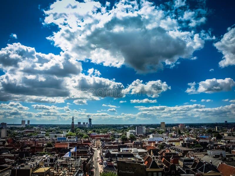 Sikt över den historiska delen av den Groningen staden under blå himmel med moln arkivfoton