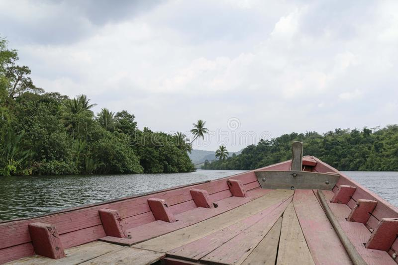 Sikt över fören av ett väl använt träfartyg som reser upp floden Kong och klipper till och med den täta djungeln royaltyfri fotografi