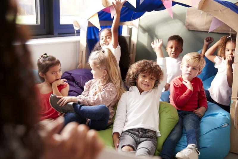 Sikt över skuldran av läraren för begynnande skola som visar en bok till en grupp av barn som sitter på bönapåsar i ett bekvämt h fotografering för bildbyråer