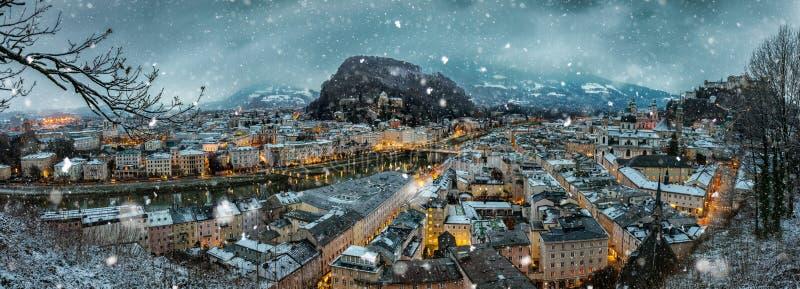 Sikt över staden av Salzburg, Österrike med fallande snö arkivbild