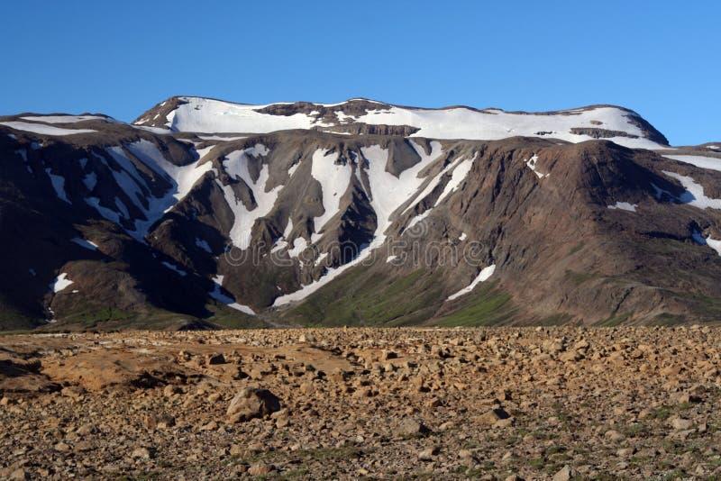 Sikt över stenig karg jordning på berget som täckas delvis med snö och is som kontrasterar med molnfri blå himmel, Island arkivbilder