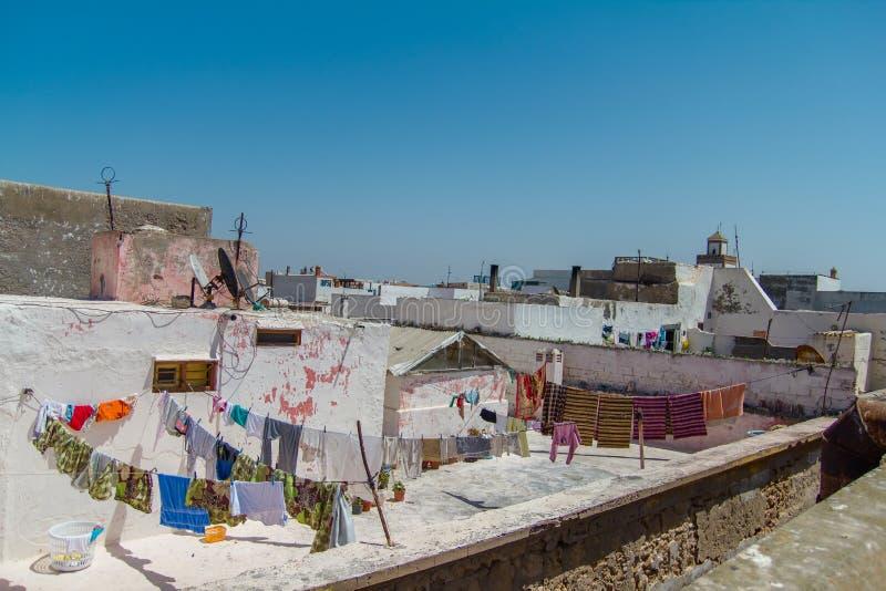 Sikt över taken av hus med olik kläder, når tvätt i den gamla arabiska staden av Essaouira arkivfoto