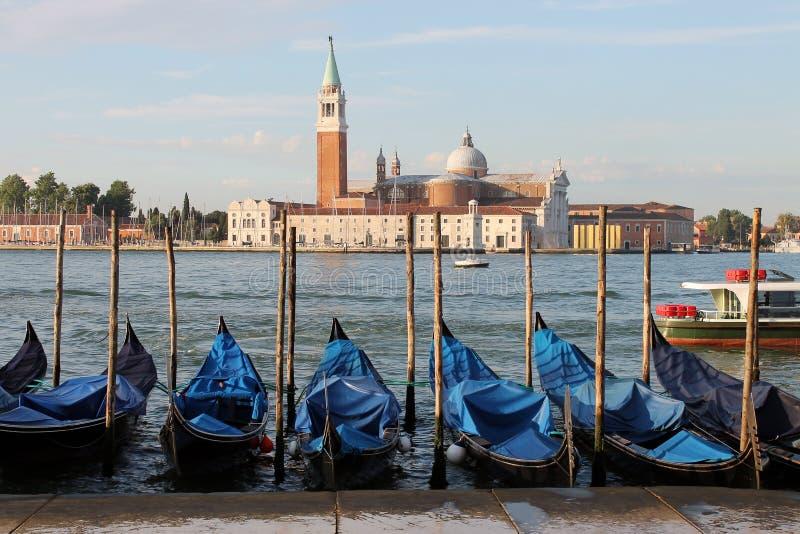 Sikt av ön av San Giorgio Maggiore i Venedig Italien med gondoler arkivfoto