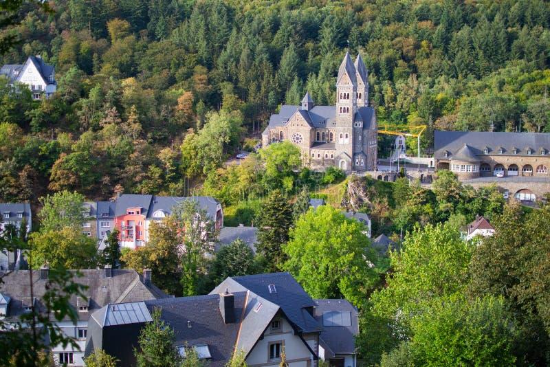 Sikt av abbotskloster av St Maurice och St Maurus av den Clervaux Clervaux abbotskloster i Luxembourg, med hus i mitt av fotografering för bildbyråer