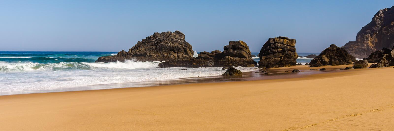 Sikt av Adraga den sandiga stranden med stenar nära Sintra, Portugal steniga kust arkivfoton