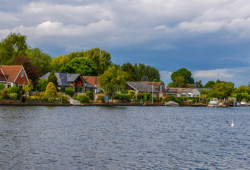 Sikt av andra sidan av floden, lokaliserade bostads- hus royaltyfri foto