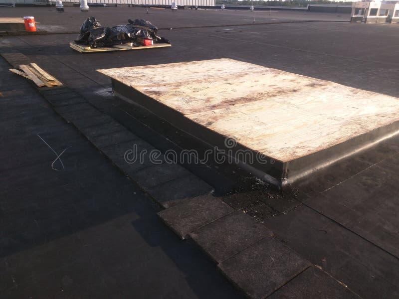 Sikt av att taklägga reparationer; Ac-trottoarkant på taket och rengöring för reklamfilm EPDM det plana upp royaltyfri fotografi