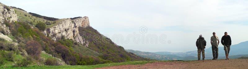 Sikt av berg med tre män Två turister som ser in i royaltyfria foton