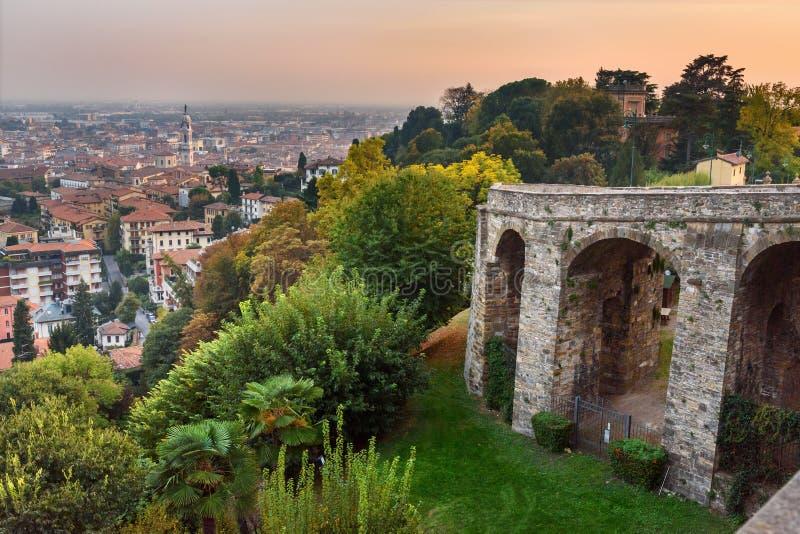 Sikt av Bergamo och den gamla bron p? via den Sant Alessandro gatan till ?vrestaden Cita Alta p? solnedg?ngen Bergamo italy arkivbild