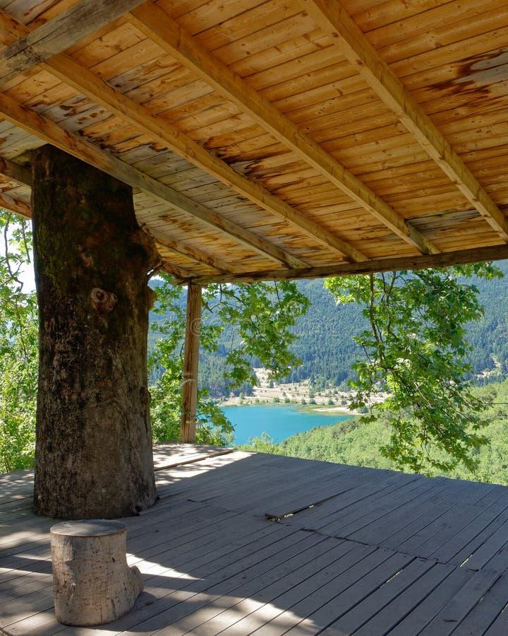 Sikt av bergsjön för blått vatten från ett gammalt öppet skjul fotografering för bildbyråer