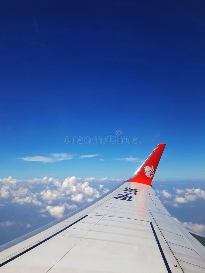 Sikt av blå himmel och moln från flygplanfönster arkivfoton