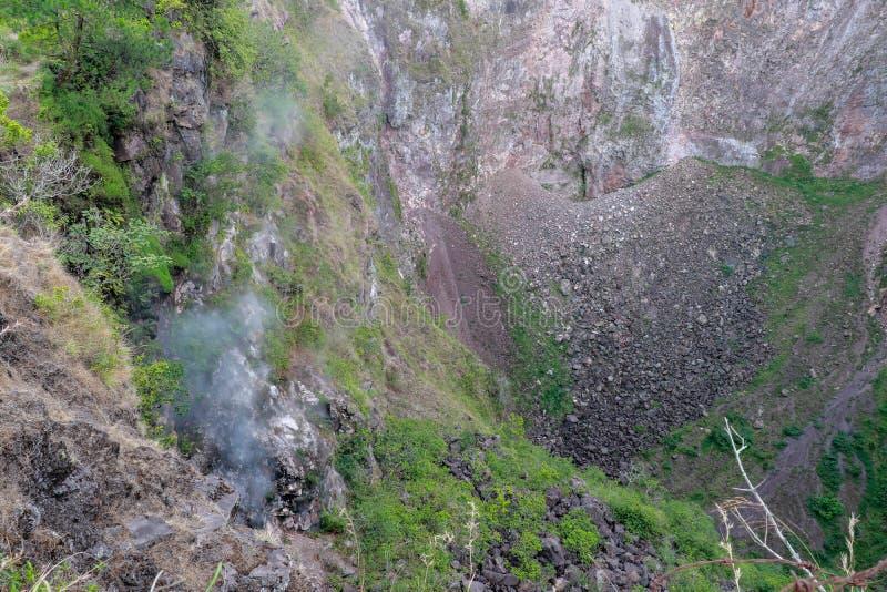 Sikt av botten av den djupa krater av den aktiva Batur vulkan i Bali Rök stiger från den branta väggen av den vulkaniska krater royaltyfri fotografi