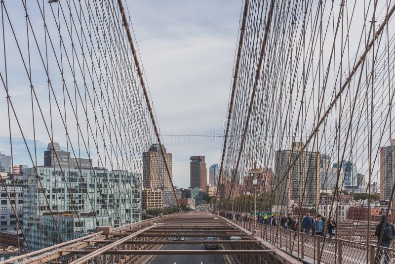 Sikt av Brooklyn från den Brooklyn bron, med kablar och stålstrukturer av bron och att gå för folk royaltyfria foton