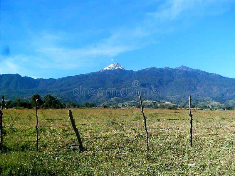 Sikt av bygden in mot den Nevado de Colima vulkan arkivbild