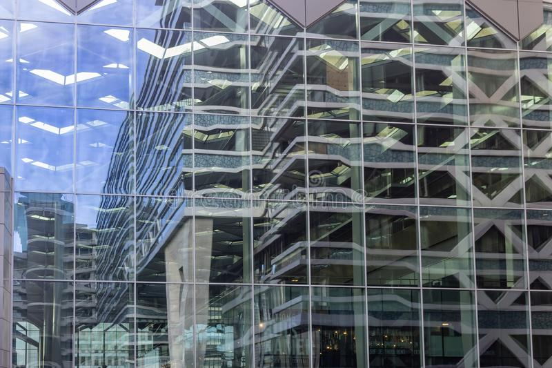 Sikt av byggnaderna runt om centralstationen, reflekterad i fönstren på sidan av huvudbyggnaden, Haag, Netherland arkivbild
