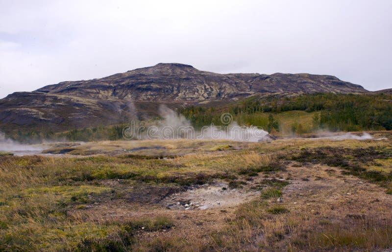 Sikt av dalen av geysers, kullar och berg som röker källor royaltyfria bilder