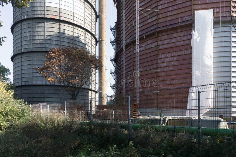 Sikt av de enorma fabrikscisternerna bak staketet royaltyfri bild