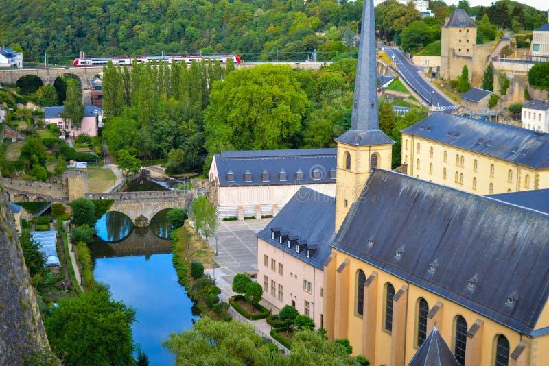 Sikt av den Alzette floden i den gamla staden av den Luxembourg staden, Luxembourg, med kyrkan för St John Church av St John elle arkivfoton