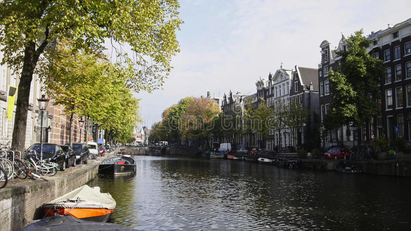 Sikt av den Amsterdam staden: otta molnig dag, höst - bilar och cyklar som parkerades längs kanalen, träd reflekterade in arkivbilder