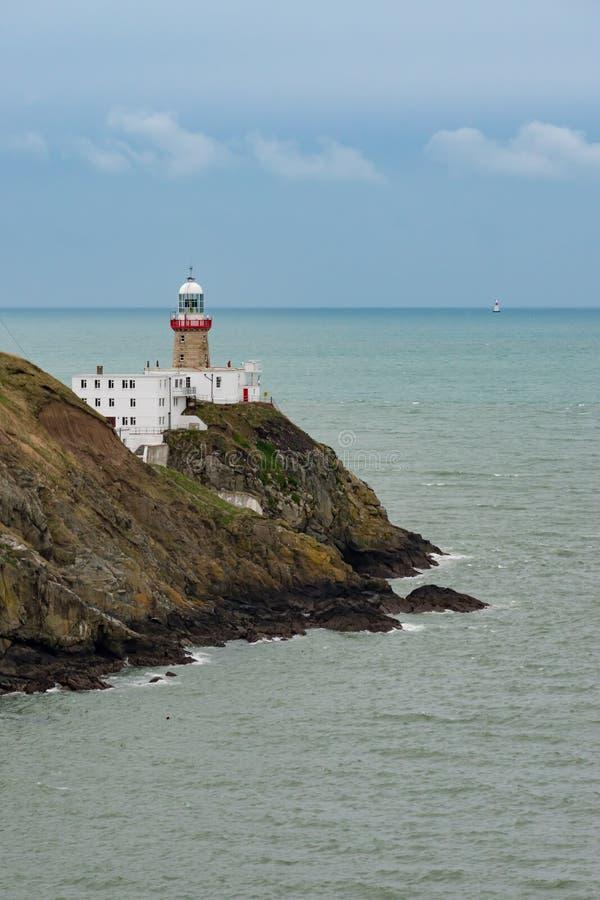Sikt av den Baily fyren på Howth de halvöliknande klipporna med en andra upplyst fyr i det irländska havet royaltyfri bild
