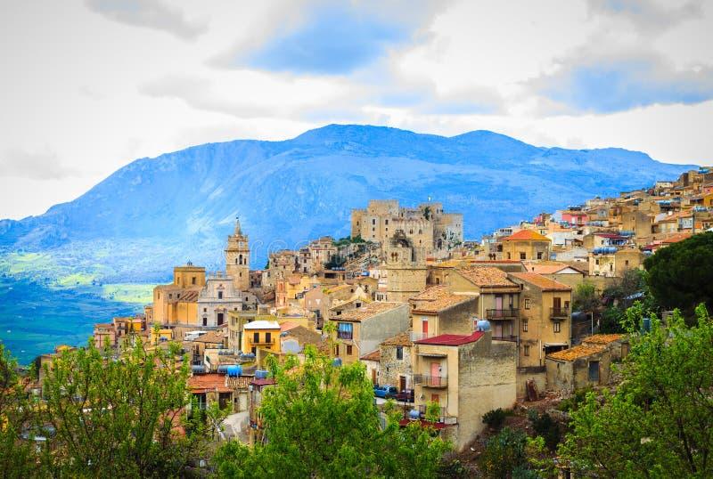 Sikt av den Caccamo staden på kullen med bergbakgrund på molnig dag i Sicilien arkivfoton