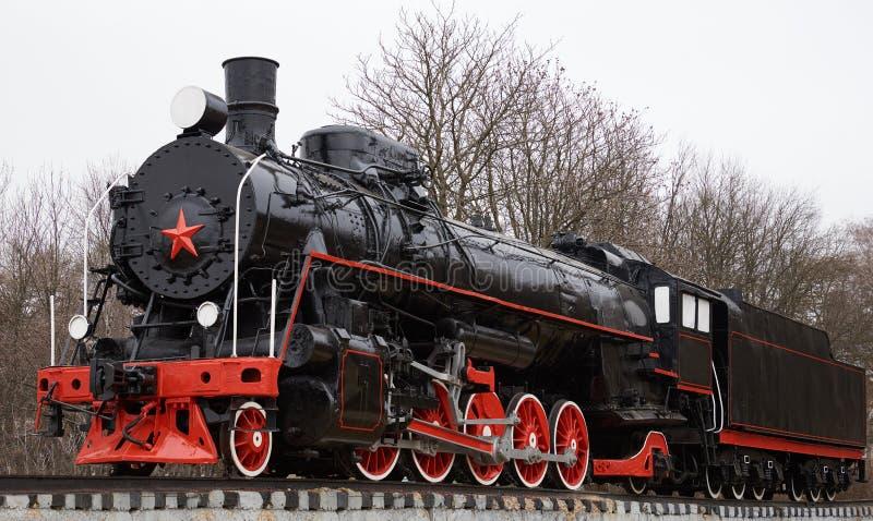 Sikt av den gamla klassiska svarta sovjetiska ångalokomotivet med den röda stjärnan på framdel arkivbilder