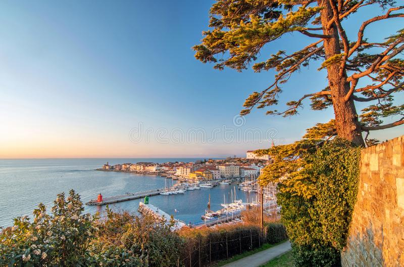 Sikt av den gamla kuststaden Piran och Adriatiskt havet som tänds av varmt aftonljus, Slovenien arkivfoton
