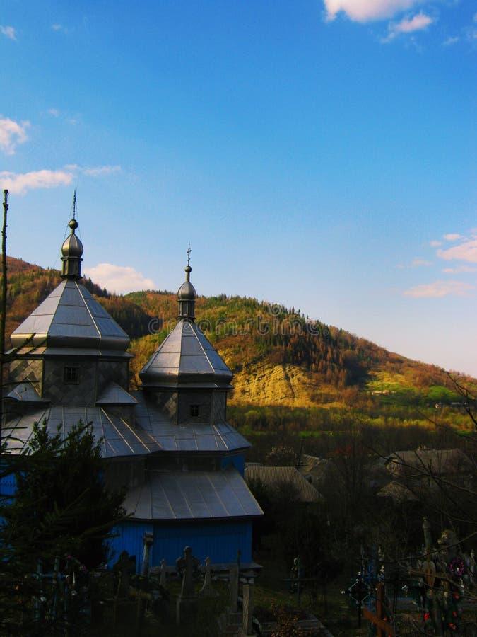 Sikt av den gamla ortodoxa kyrkan och kyrkogården i skogen arkivbilder