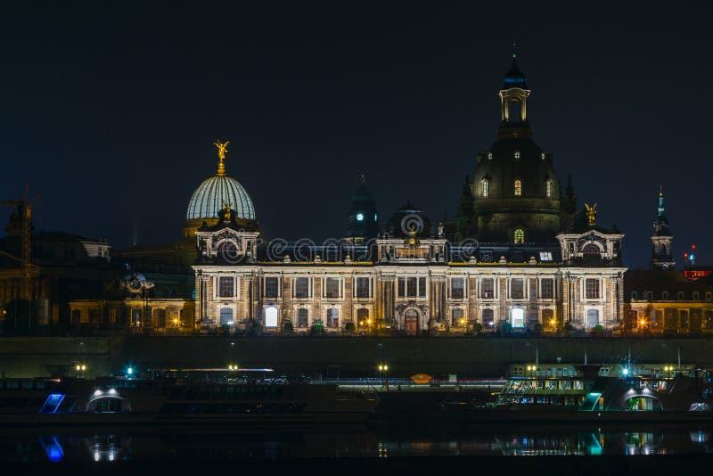 Sikt av den gamla staden av Dresden på natten med en sikt av vatten och reflexionen av staden såväl som, kyrkor, torn och buien arkivbilder