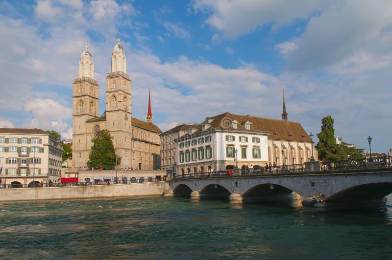 Sikt av den Grossmunster kyrkan, townhall och bron i Zurich, Schweiz arkivbild
