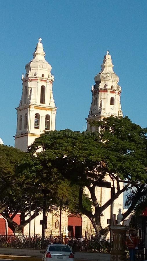 Sikt av den härliga kyrkan som förbiser den storslagna plazaen i i stadens centrum Merida, Mexico royaltyfri foto
