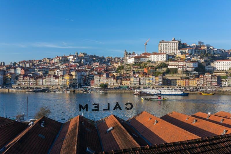 Sikt av den historiska staden av Porto med berömda broPonte dom Luis, kabelbilar och fartyg på den Douro floden royaltyfri bild
