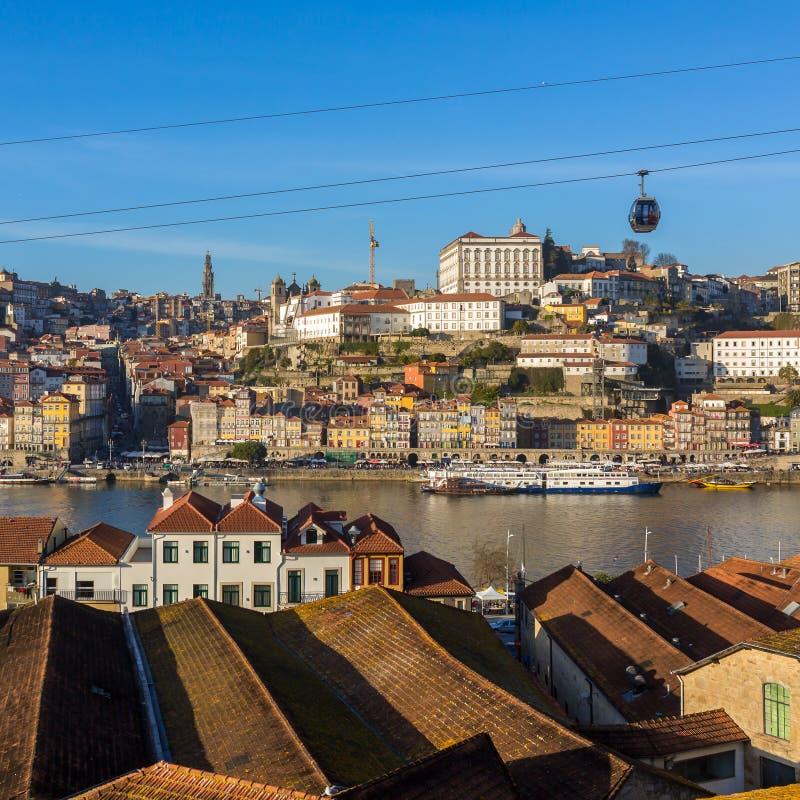 Sikt av den historiska staden av Porto med berömda broPonte dom Luis, kabelbilar och fartyg på den Douro floden, Portugal royaltyfri bild