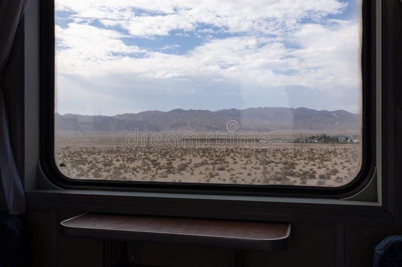 Sikt av den Kumtag öknen i det Gansu landskapet från fönstret av ett drev arkivfoton
