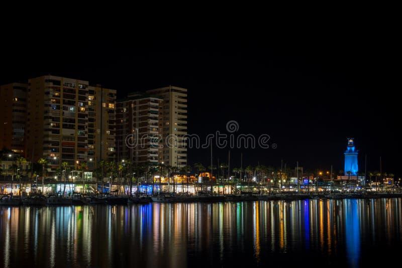 Sikt av den Malaga staden och fyren och deras reflexioner på wate royaltyfria foton