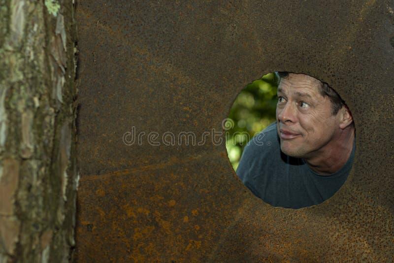 Sikt av den manliga framsidan igenom i järnplattahålet Förvånat lyckligt mandanandehål i järnplatta fotografering för bildbyråer