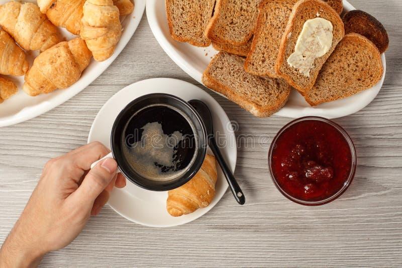 Sikt av den manliga handinnehavkoppen av svart kaffe på tabellen med royaltyfria foton