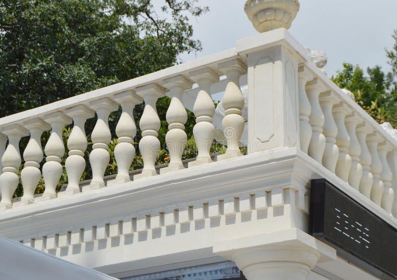 Sikt av den romantiska vita balkongen, terrass med baluster, vit stenräcke royaltyfri foto