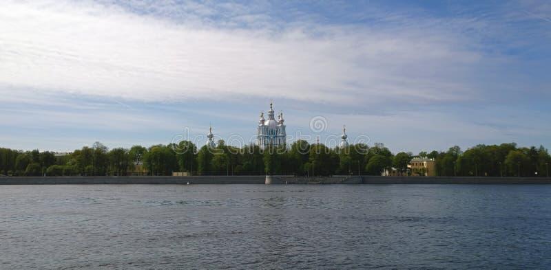 Sikt av den Smolny domkyrkan i St Petersburg från den Sverdlovskaya invallningen Den Neva floden i förgrunden arkivfoton