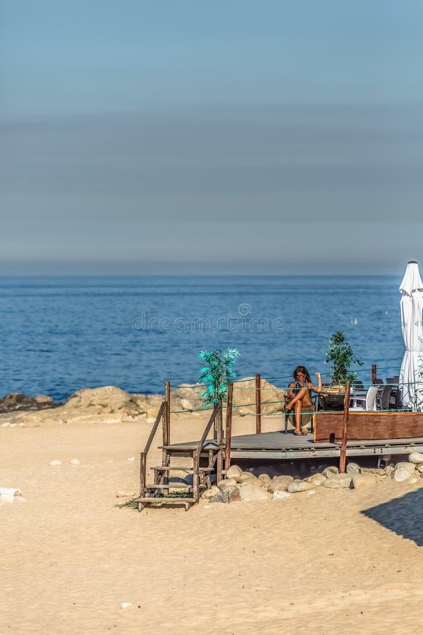 Sikt av den teknologiska höga kvinnan som tar sunbath och använder hennes mobiltelefon på strandklubban, hav som bakgrund, i Port royaltyfria bilder