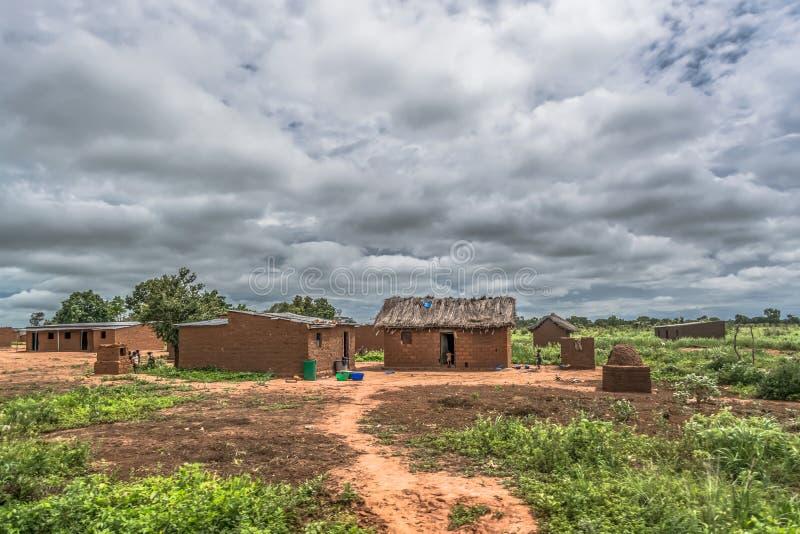 Sikt av den traditionella byn, halmtäckte hus på taket och terrakottategelstenväggar, ungar som utanför spelar arkivfoto